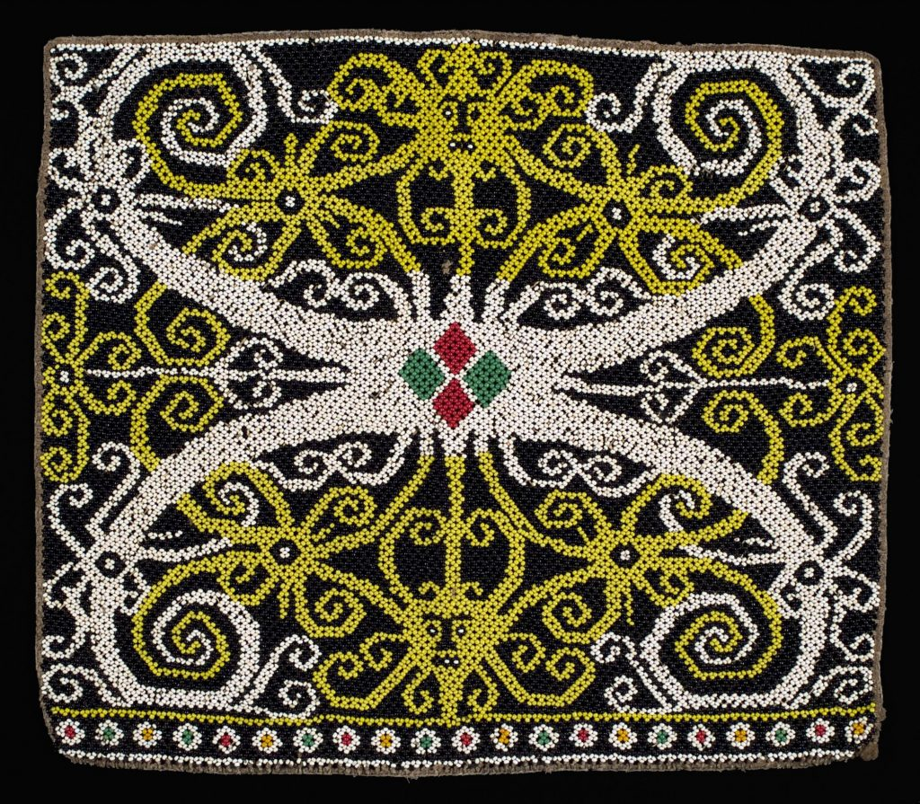 Charge symmetry on the magnetic axis is suggested by the red and green beads of this baby carrier from Borneo.