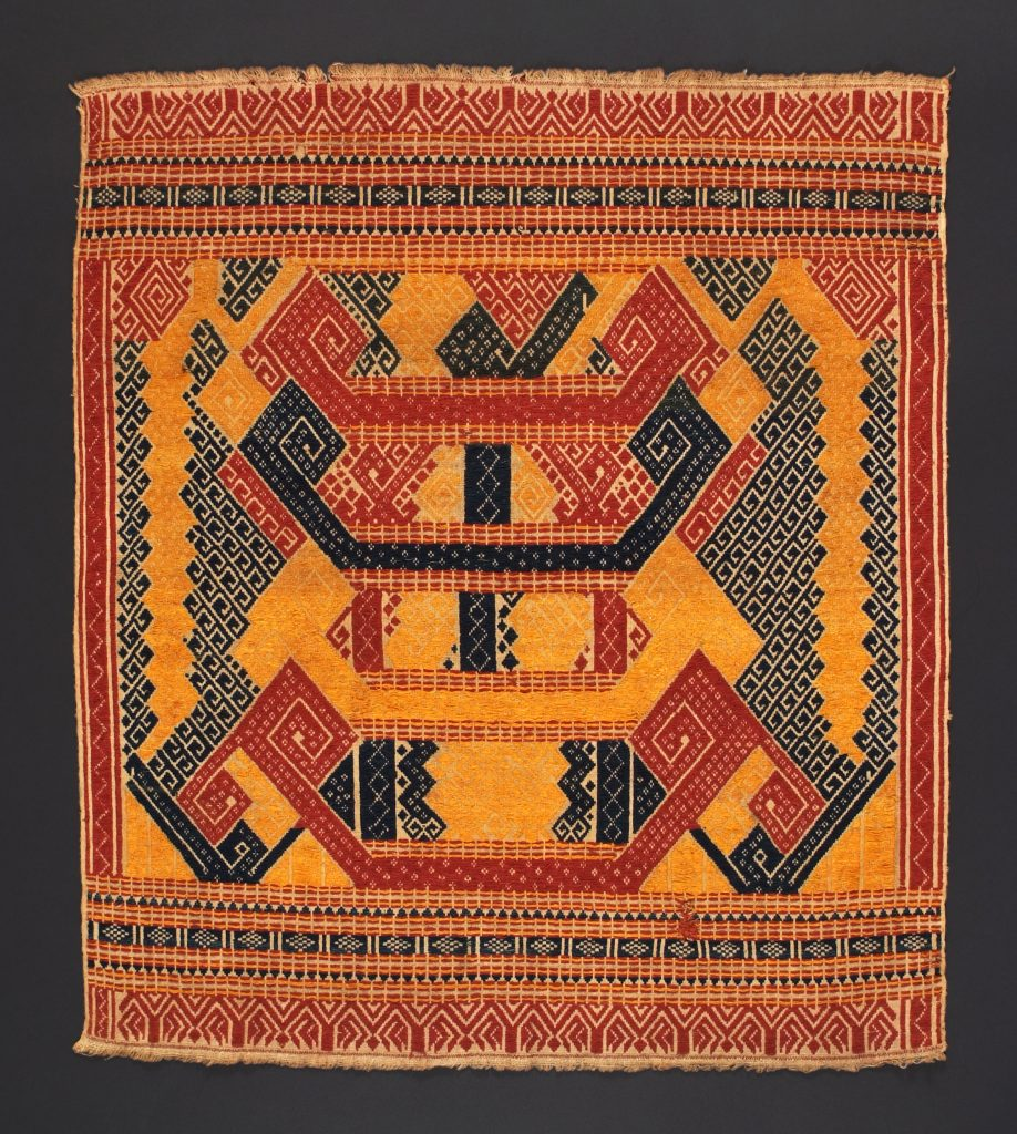 The mass depends on a difference between two quantities in tension with each other, somewhat like the warp and weft of this weaving from Indonesia.